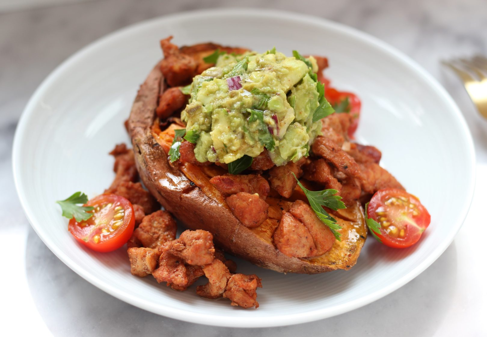 Patate douce rôtie au four accompagnée de guacamole et porc sauté au paprika